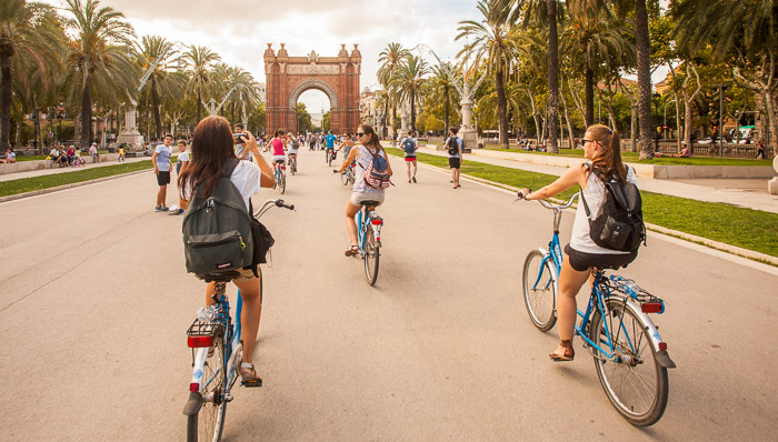 Women with backpacks bike through Barcelona on a sunny afternoon.