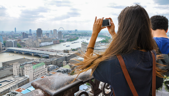 Young woman takes a photo from the London Crown Jewels overlooking the Thames River