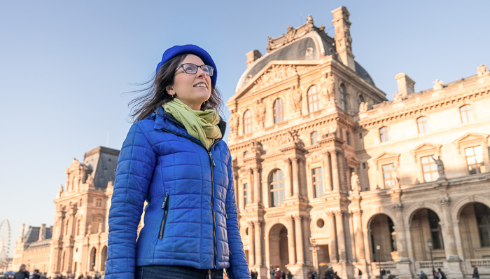 Woman wearing a blue coat and blue jacket walks around the center of Paris, France on a sunny afternoon