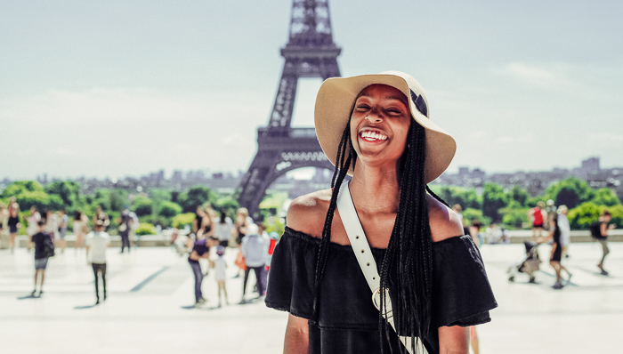 Young woman stands in front of the Eiffel Tower in Paris with a hat and black top, smiling
