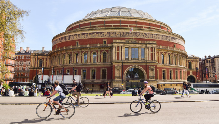 People bike around London on a sunny day sightseeing next tp Royal Albert Hall