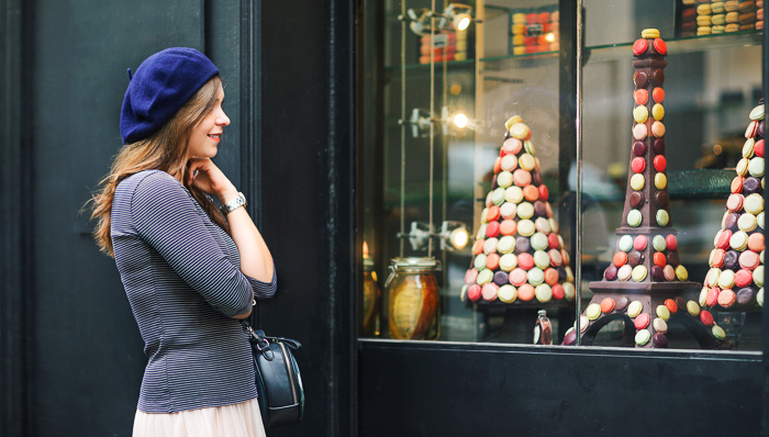 Young woman wearing a blue beret and striped shirt looks at macarons in a window display in Paris, France