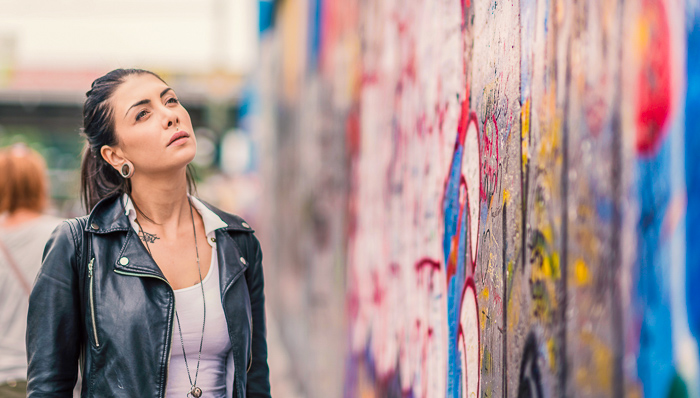 Young woman squints at the art on the Berlin Wall on a sunny day
