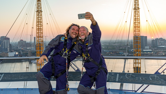 Two men take a selfie after climbing to the top of the O2 arena in London. They are smiling and laughing, close friends.
