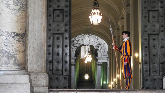Entry to the Vatican guarded by a guard dressed in the traditional blue, red, and orange striped uniform.