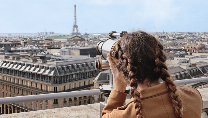 Woman with braids looks at the Eiffel Tower through coin binoculars in Paris.