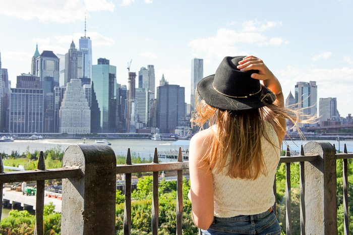 Young woman wearing a hat overlooks the New York City skyline and the Hudson River