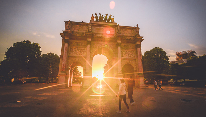 Sunset photo of the Arc de Triomph in Paris, France with people walking nearby and sunlight streaming through the arch