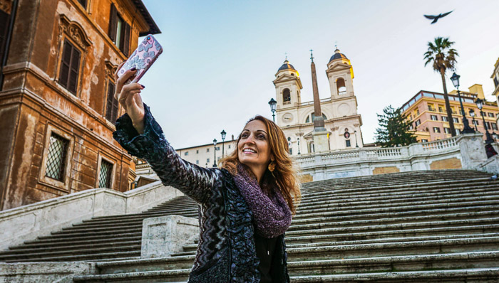 Woman takes a selfie at the bottom of the Spanish Steps in Rome
