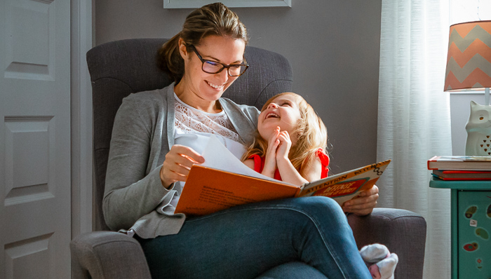 Mother and daughter read a storybook in a chair in the afternoon. Little girl laughs.