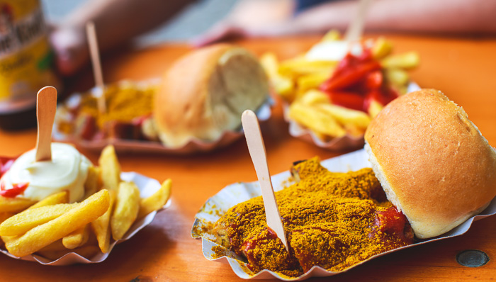 Traditional German street food - currywurst, served with french fries on a disposable paper tray