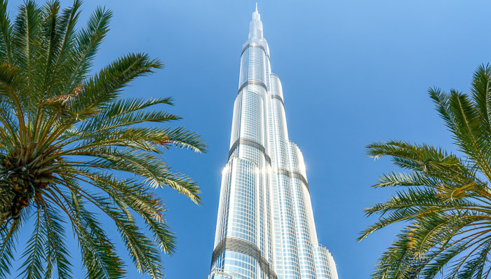 Picture from below of the glittering Burj Khalifa with palm trees in the foreground