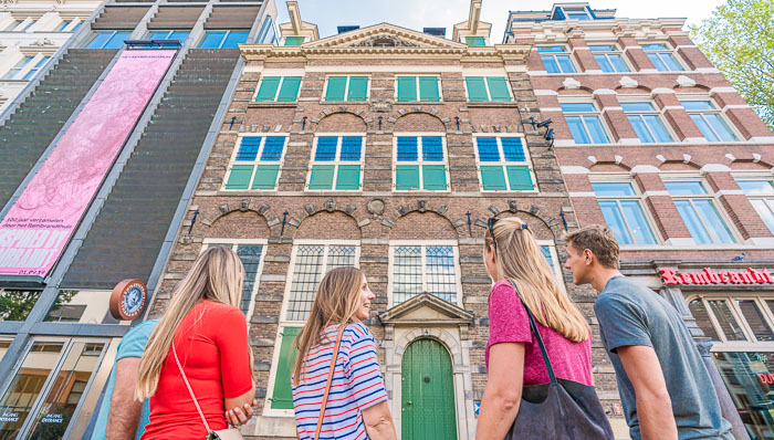 Tourists look up at the narrow houses of Amsterdam, Holland, The Netherladns.