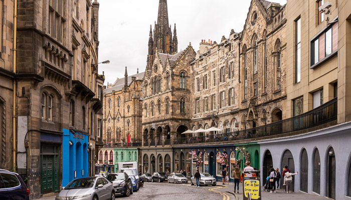 Shot of downtown Edinburgh, Scotland during the afternoon. Old buildings, cars and people walking
