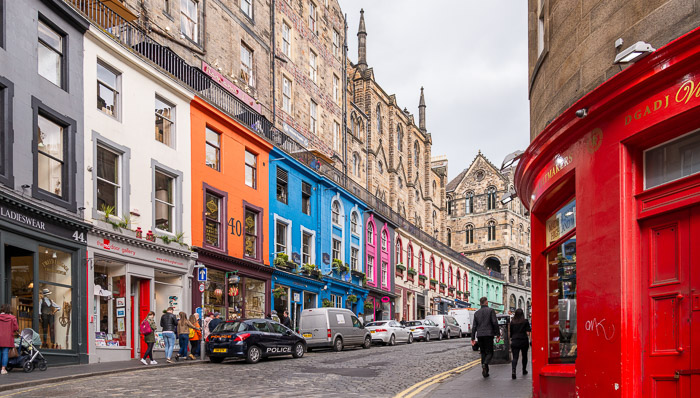 Colorful shops and houses line the streets of central Edinburgh, Scotland. Painted in red, orange, blue, white, pink and green