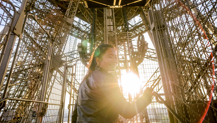 Young woman smiling inside the Eiffel Tower in Paris with sunlight shining through