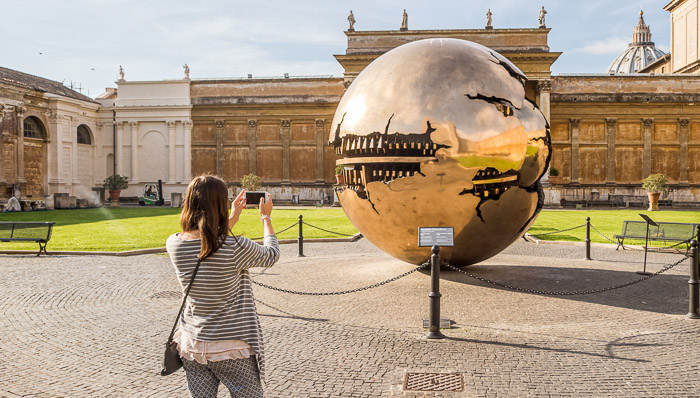 Young woman in striped shirt takes a photo of the copper statue outside of the Vatican in Rome.