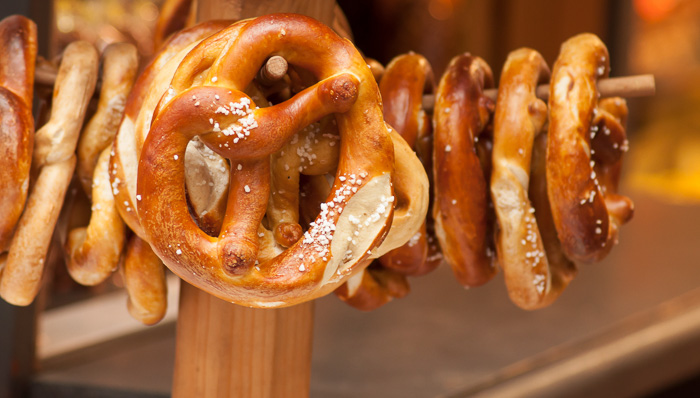 Photo of Bavarian pretzels with salt hanging on a wooden stand.