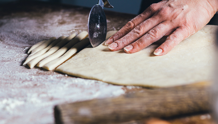 Woman cuts dough into strips. Only her flour-covered hand can be seen.