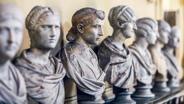 Marble statue busts of famous ancient Romans on a table.