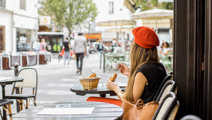 French woman sitting at cafe with coffee and croissants.