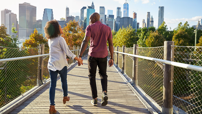Young couple walks along a bridge in New York City while holding hands on a sunny day.