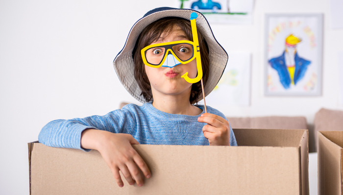Little boy sits in a cardboard box wearing a blue striped shirt. Has a hat on and yellow scuba diving mask.