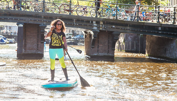 Woman does stand up paddle board in the canals of Amsterdam, Holland, The Netherlands