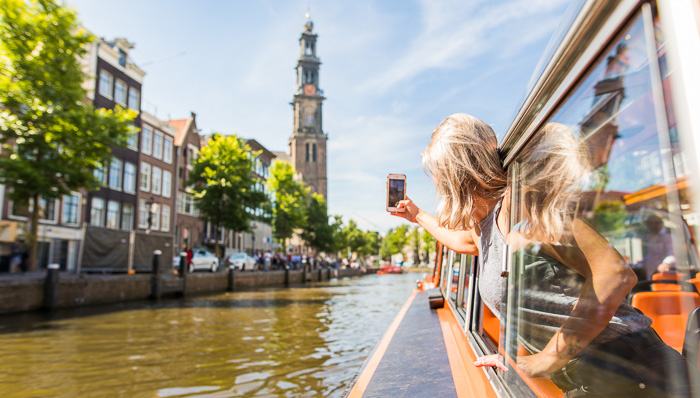 Blonde woman takes a photo of Amsterdam from a canal cruise boat.