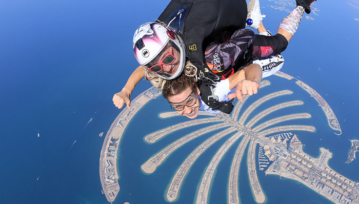 A skydiver with a view of the Dubai Palm below them.