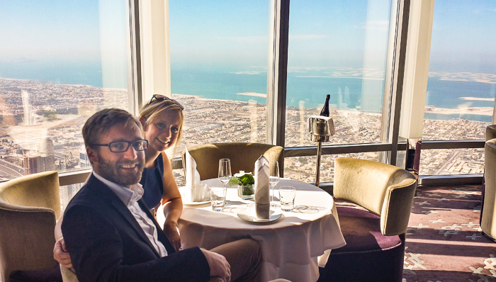 A middle-aged couple sitting in one of the Burj Khalifa restaurants overlooking Dubai. They are having a drink.