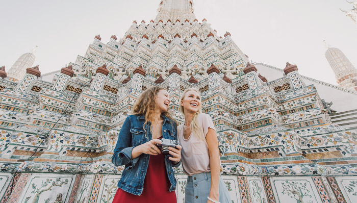 Two young women stand in front of Bangkok landmark laughing.