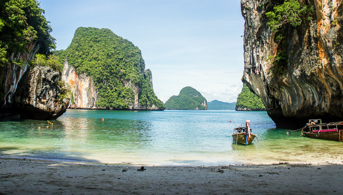 Photo of a beach in Thailand with greenery and a small fishing boat in the afternoon.