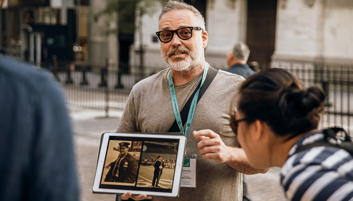Tour guide in New York City uses an iPad to show tourists photos of figures he's speaking about on historic tour.