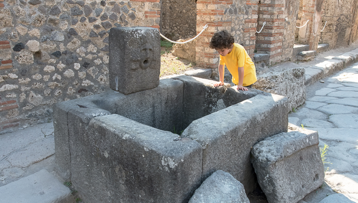 Kid with yellow t-shirt watches inside stones in Pompeii
