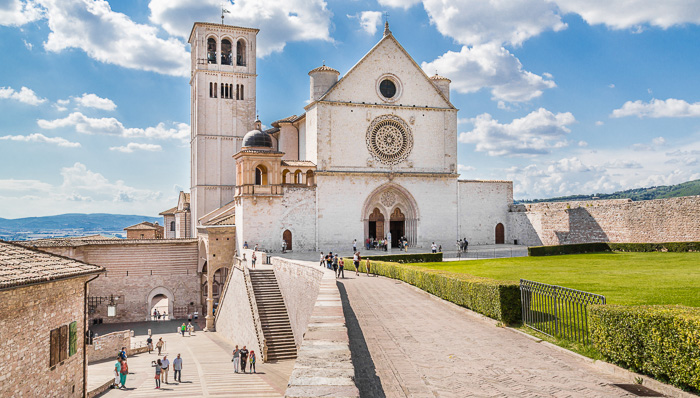 The Basilica of St. Francis in Assisi and Umbria region, the bell tower and the basilica are made of white stone which contrats with the green gardens around.