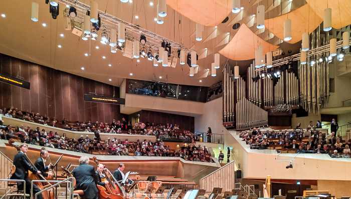 People watching a concert inside the Philharmonic