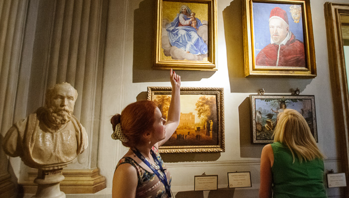Young woman pointing at the paintings on the wall, while another woman stares at them