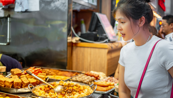 Young lady looking at different dish at an asian street market, gauging the hot pans of food in front of her