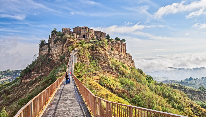Landscape of Civita di Bagnoregio only few hours from Rome, people walking on the bridge to reach to top of the hill