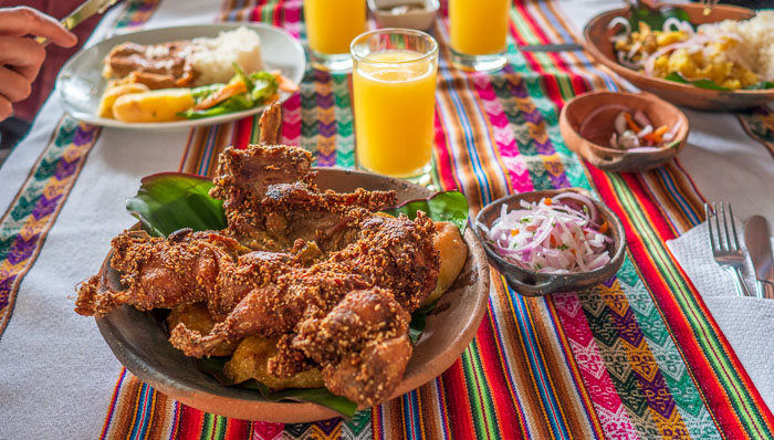 roasted guined pig, the traditional andean dish served in ecuardor and peru served on a table with Pico de gallo on the side