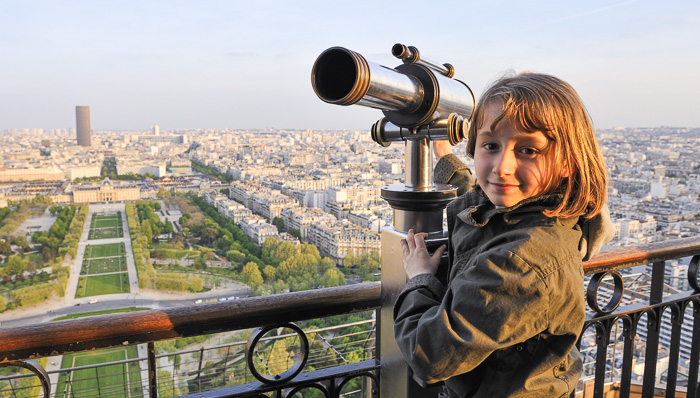 Kid standing in front of a telescope to look down at the city