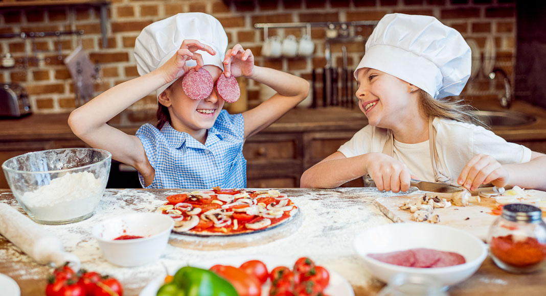Two young girls making fresh pizza. One of them is hiding her eyes with salami.