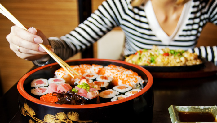 A round plate of sushis, makis and salmon rolls ready to be eaten by a women with chopsticks and a stripes shirt.