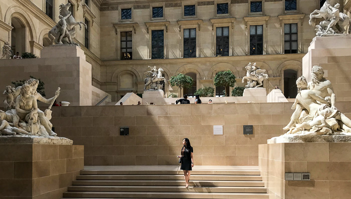Woman walking down the stairs looking at the sculptures