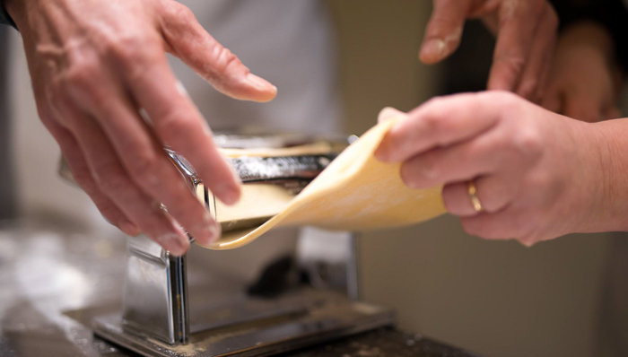 Hands on: hands of two people pulling the 'in the making' dough out of the pasta making machine's pair of rolls.