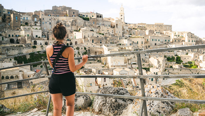 Sassi di Matera village made directly inside the rock of the hill. A young lady is facing the hill looking at the white houses made from the stone.