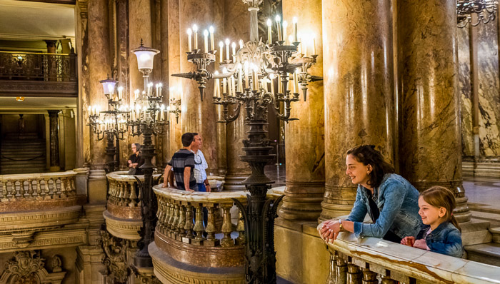 People looking around the inside the opera, chandeliers and big columns