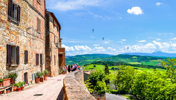 Panoramic view Pienza in the valley in Val d'Orcia region. Many houses made of stones are dominating the valley of wine fields.