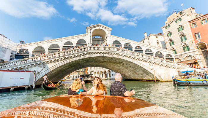Crossing Venetian bridges on a gondola is part of the must dos.